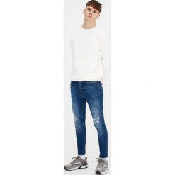 Postrzępione jeansy carrot fit. Niebieskie jeansy męskie relaxed fit Pull&Bear. Za 139,00 zł.