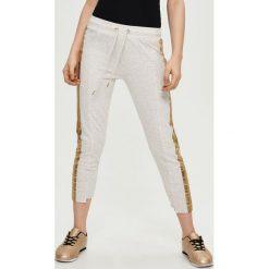 Spodnie damskie: Dresowe spodnie z lampasem – Kremowy
