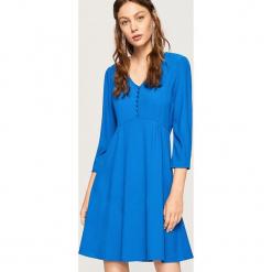 Sukienka z dekoltem V - Niebieski. Białe sukienki z falbanami marki Reserved, l, z dzianiny. Za 119,99 zł.