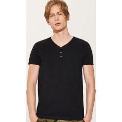 Gładki t-shirt z guzikami - Czarny. Czarne t-shirty męskie marki KIPSTA, z poliesteru, do piłki nożnej. Za 35,99 zł.