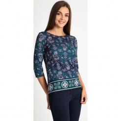 Bluzka z orientalnym wzorem QUIOSQUE. Zielone bluzki z odkrytymi ramionami marki QUIOSQUE, w jednolite wzory, z dzianiny, z krótkim rękawem. W wyprzedaży za 89,99 zł.
