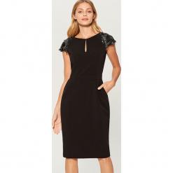 Dopasowana sukienka z ozdobnymi rękawami - Czarny. Czerwone sukienki z falbanami marki Mohito, l, w koronkowe wzory. Za 169,99 zł.