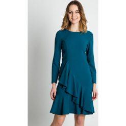 Morska sukienka z falbanami  BIALCON. Zielone sukienki balowe marki BIALCON, na imprezę, ze splotem, z falbankami, z długim rękawem, baskinki. W wyprzedaży za 241,00 zł.