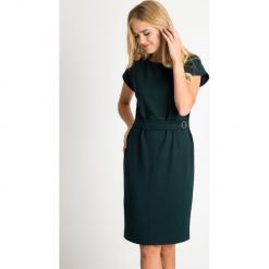 Zielona sukienka z ozdobnym paskiem QUIOSQUE. Zielone sukienki balowe marki QUIOSQUE, do pracy, na jesień, w paski, z dzianiny, z kopertowym dekoltem, z krótkim rękawem, mini, dopasowane. Za 199,99 zł.