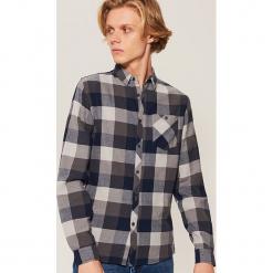 Koszula w kratkę - Wielobarwn. Czarne koszule męskie w kratę marki KIPSTA, z poliesteru, do piłki nożnej. Za 79,99 zł.