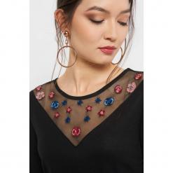 Koszulka z haftem i koralikami. Czarne bluzki z odkrytymi ramionami marki bonprix, w kwiaty, z dekoltem w serek. Za 69,99 zł.