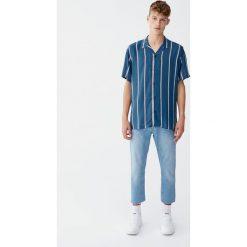 Jeansy o prostym kroju z efektem zużycia. Niebieskie jeansy męskie z dziurami Pull&Bear. Za 109,00 zł.