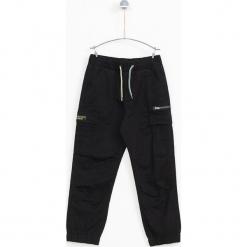 Spodnie w kolorze czarnym. Czarne spodnie chłopięce marki Lemon Fashion. W wyprzedaży za 89,95 zł.