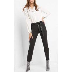 Spodnie w kant z wiązaniem. Czarne rurki damskie marki Orsay, w paski, z bawełny. W wyprzedaży za 90,00 zł.