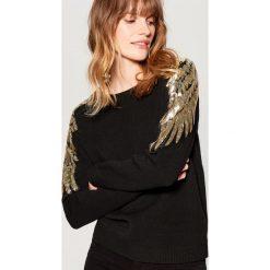 Sweter z cekinową aplikacją - Czarny. Czarne swetry klasyczne damskie Mohito, l. Za 119,99 zł.