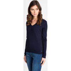 Granatowy sweter z kamieniami QUIOSQUE. Niebieskie swetry klasyczne damskie QUIOSQUE, z dzianiny, z dekoltem w serek. W wyprzedaży za 79,99 zł.