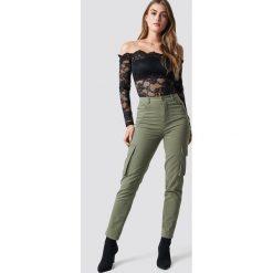 Pamela x NA-KD Spodnie z wysokim stanem Army - Green. Zielone spodnie z wysokim stanem Pamela x NA-KD. Za 202,95 zł.