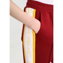 Calvin Klein Jeans SIDE STRIPE TRACK PANTS Spodnie treningowe cabernet. Czerwone jeansy damskie Calvin Klein Jeans, xl, z bawełny. W wyprzedaży za 381,75 zł.