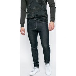 Wrangler - Jeansy Strangler Rinse. Niebieskie jeansy męskie Wrangler, z aplikacjami, z bawełny. W wyprzedaży za 219,90 zł.