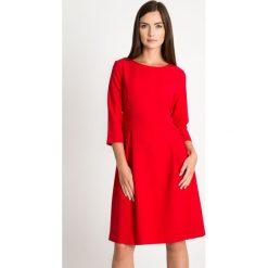 Czerwona rozkloszowana sukienka QUIOSQUE. Czerwone sukienki QUIOSQUE, do pracy, z tkaniny, biznesowe, z dekoltem w łódkę, z długim rękawem, rozkloszowane. W wyprzedaży za 139,99 zł.