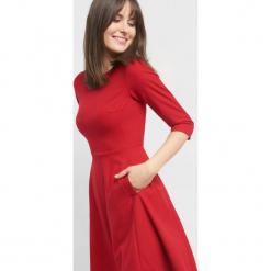 Rozkloszowana sukienka. Różowe sukienki koktajlowe marki numoco, l, z dekoltem w łódkę, oversize. Za 139,99 zł.