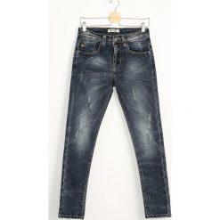 Granatowe Jeansy Steep. Czarne jeansy męskie z dziurami marki Born2be, l, z aplikacjami, z dresówki. Za 54,99 zł.