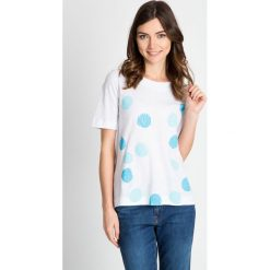 Biała bluzka w błękitna grochy QUIOSQUE. Białe bluzki z odkrytymi ramionami QUIOSQUE, w geometryczne wzory, z bawełny, klasyczne, z dekoltem w łódkę, z krótkim rękawem. W wyprzedaży za 19,99 zł.