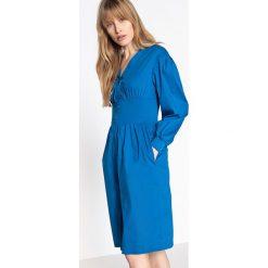 Sukienki: Sukienka rozkloszowana, zapinana na guziki z przodu, z gumką