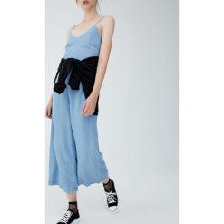 Długi kombinezon jeansowy z węzłem na plecach. Niebieskie kombinezony damskie marki Pull&Bear. Za 159,00 zł.