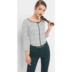 Koszulka w kwiaty z lamówką. Białe bluzki z odkrytymi ramionami marki Orsay, s, w kwiaty, z bawełny, eleganckie, z kokardą, z długim rękawem. Za 69,99 zł.