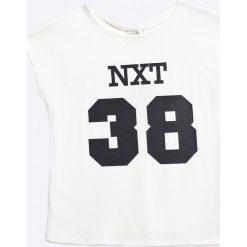 Name it - Top dziecięcy 110-164 cm. Białe bluzki dziewczęce marki Name it, z nadrukiem, z bawełny, z okrągłym kołnierzem. W wyprzedaży za 16,90 zł.