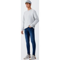 Ciemnoniebieskie jeansy skinny fit z efektem sprania. Niebieskie rurki męskie Pull&Bear, z denimu. Za 119,00 zł.