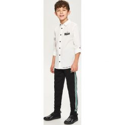 Spodnie dresowe z lampasami - Czarny. Czarne chinosy chłopięce Reserved, z dresówki. W wyprzedaży za 29,99 zł.