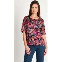 Oversize'owa bluzka z kolorowym wzorem QUIOSQUE. Czerwone bluzki nietoperze marki QUIOSQUE, w kolorowe wzory, z dzianiny, z dekoltem w łódkę. Za 139,99 zł.