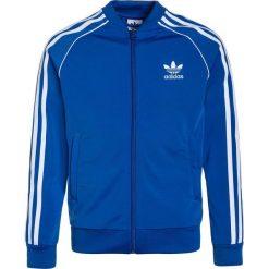 Adidas Originals Kurtka sportowa blue. Szare kurtki dziewczęce sportowe marki adidas Originals, na co dzień, z nadrukiem, z bawełny, z okrągłym kołnierzem, proste. W wyprzedaży za 179,10 zł.