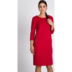 Malinowa plisowana sukienka z dzianiny QUIOSQUE. Różowe sukienki balowe marki QUIOSQUE, do pracy, z dzianiny, z klasycznym kołnierzykiem, z długim rękawem, proste. W wyprzedaży za 99,99 zł.
