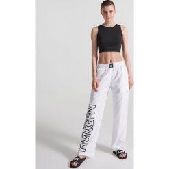 Sportowe spodnie z napisami - Biały. Białe spodnie sportowe damskie marki Reserved, l, z napisami. W wyprzedaży za 39,99 zł.