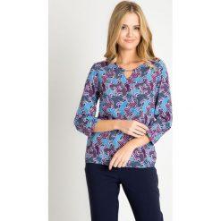 Bluzka z fioletowym wzorem QUIOSQUE. Fioletowe bluzki asymetryczne QUIOSQUE, ze skóry, biznesowe, z klasycznym kołnierzykiem. W wyprzedaży za 39,99 zł.