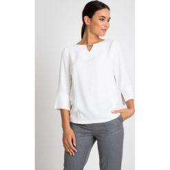 Biała bluzka z koralikami przy dekolcie QUIOSQUE. Białe bluzki asymetryczne QUIOSQUE, z tkaniny, biznesowe, z klasycznym kołnierzykiem. W wyprzedaży za 99,99 zł.