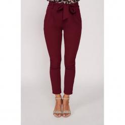 Spodnie w kolorze bordowym. Czerwone spodnie z wysokim stanem marki Dioxide, w paski. W wyprzedaży za 99,95 zł.