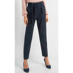 Spodnie w kant z paskiem. Niebieskie spodnie z wysokim stanem Orsay, w ażurowe wzory, z elastanu. Za 119,99 zł.