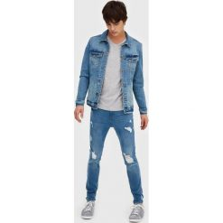 Niebieskie jeansy skinny fit z przetarciami. Szare jeansy męskie relaxed fit marki Pull & Bear, okrągłe. Za 69,90 zł.