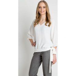 Bluzka w kolorze ecru z ozdobnym wiązaniem u dołu BIALCON. Białe bluzki nietoperze BIALCON, eleganckie, z dekoltem w serek. Za 179,00 zł.