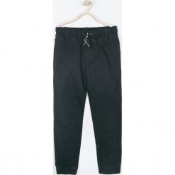 Spodnie. Czarne chinosy chłopięce TRAVELLER, z bawełny. Za 99,90 zł.