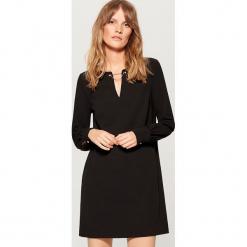 Sukienka z biżuteryjną ozdobą - Czarny. Czarne sukienki z falbanami marki Mohito, l. Za 99,99 zł.