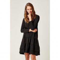 Sukienka w kolorze czarnym. Czarne sukienki z falbanami marki SCUI, s, z falbankami, midi. W wyprzedaży za 149,95 zł.