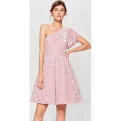 Sukienka z welurowym zdobieniem - Różowy. Różowe sukienki z falbanami marki numoco, l, z dekoltem w łódkę, oversize. W wyprzedaży za 99,99 zł.