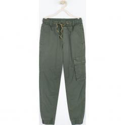 Spodnie. Brązowe chinosy chłopięce TRAVELLER, z bawełny. Za 109,90 zł.