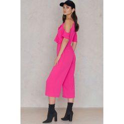 Boohoo Kombinezon z wycięciami na ramionach i falbaną - Pink. Czarne kombinezony damskie marki Boohoo, l, z poliesteru. W wyprzedaży za 36,59 zł.