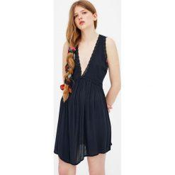 Sukienka z dekoltem w serek. Niebieskie sukienki z falbanami marki Pull&Bear. Za 89,90 zł.