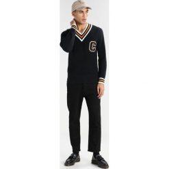 Calvin Klein SARET VARSITY Sweter black. Pomarańczowe kardigany męskie marki Calvin Klein, l, z bawełny, z okrągłym kołnierzem. W wyprzedaży za 374,50 zł.