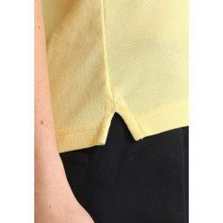 Lacoste Sport RYDER CUP Koszulka sportowa jaune/blanc. Żółte bluzki sportowe damskie Lacoste Sport, z bawełny, polo. Za 369,00 zł.