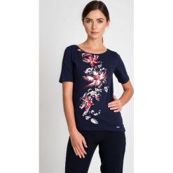 Granatowa bluzka z kwiatową aplikacją QUIOSQUE. Białe bluzki asymetryczne QUIOSQUE, z aplikacjami, z bawełny, eleganckie, z dekoltem w łódkę, z krótkim rękawem. W wyprzedaży za 29,99 zł.