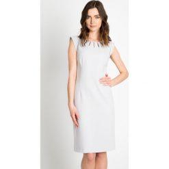 Szara sukienka z ozdobnym dekoltem QUIOSQUE. Szare sukienki na komunię marki QUIOSQUE, na imprezę, w kolorowe wzory, z wełny. W wyprzedaży za 79,99 zł.