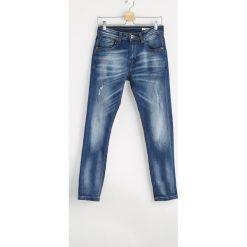 Niebieskie Jeansy Dashes. Czarne jeansy męskie z dziurami marki Born2be, l, z aplikacjami, z dresówki. Za 49,99 zł.